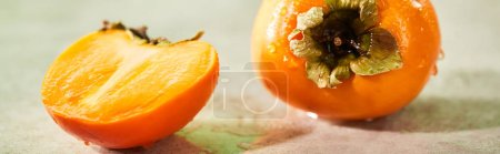 Photo for Panoramic shot of whole and cut persimmons on marble surface - Royalty Free Image