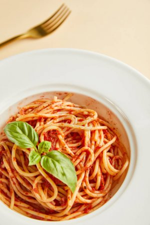 Photo for Selective focus of delicious spaghetti with tomato sauce and basil in plate near fork on yellow background - Royalty Free Image