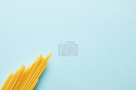 Photo pour Vue du dessus des spaghettis crus sur fond bleu avec espace de copie - image libre de droit