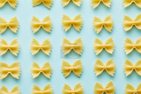 Photo pour À plat avec farfalle cru sur fond bleu - image libre de droit