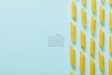 Photo pour Pose plate avec penne brute sur fond bleu avec espace de copie - image libre de droit
