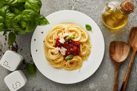 top view of delicious spaghetti with tomato sauce on plate near basil leaves and oil on grey textured surface