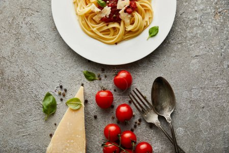Photo for Top view of delicious spaghetti with tomato sauce on plate near cheese, tomatoes and cutlery on grey textured surface - Royalty Free Image