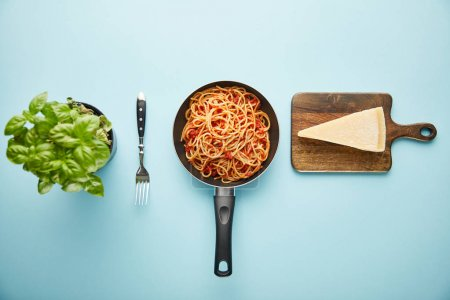 Photo for Flat lay with delicious spaghetti with tomato sauce in frying pan near basil leaves and parmesan cheese on blue background - Royalty Free Image