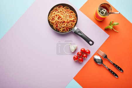 Photo for Flat lay with delicious spaghetti with tomato sauce in frying pan near ingredients on red, blue and violet background - Royalty Free Image