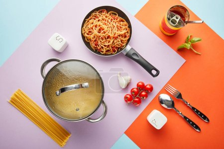 Photo for Flat lay with delicious spaghetti with tomato sauce ingredients and cooking utensils on red, blue and violet background - Royalty Free Image
