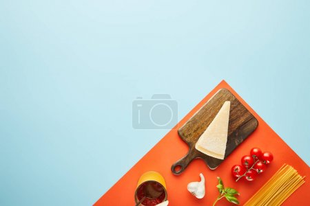 flat lay with delicious pasta with tomato sauce ingredients on blue, red background