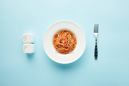 Photo for Flat lay with delicious spaghetti with tomato sauce near fork, salt and pepper shakers on blue background - Royalty Free Image