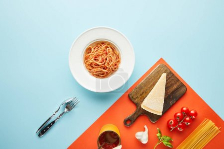Photo for Flat lay with delicious spaghetti with tomato sauce in plate near cutlery and ingredients on blue, red background - Royalty Free Image