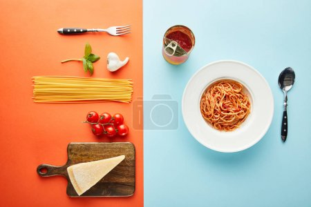 Photo for Flat lay with delicious spaghetti with tomato sauce in plate near cutlery and ingredients on blue, red and yellow background - Royalty Free Image