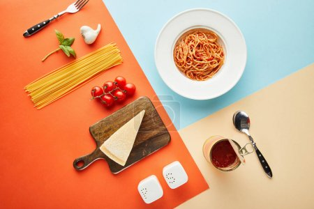 Foto de Flat lay with delicious spaghetti with tomato sauce in plate near cutlery and ingredients on blue, red and yellow background - Imagen libre de derechos