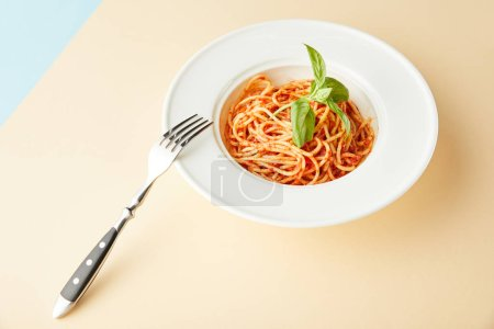 Photo for Spaghetti with tomato sauce in plate near fork on blue and yellow background - Royalty Free Image