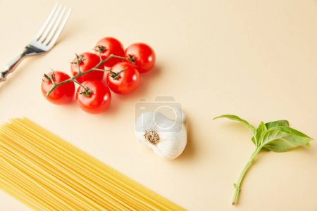 Photo for Raw spaghetti, garlic, tomatoes, basil and fork on yellow background - Royalty Free Image