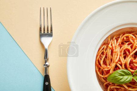 top view of delicious spaghetti with tomato sauce in plate near fork on blue and yellow background