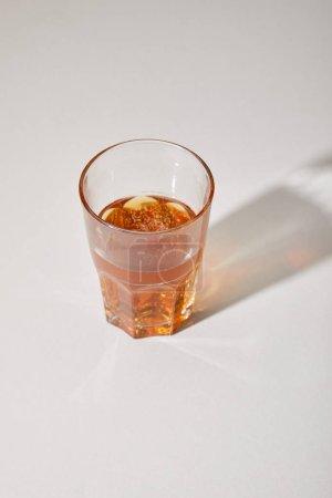 Photo pour Verre de bière fraîche sur surface blanche avec ombre - image libre de droit