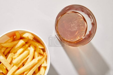 top view of beer in glass near delicious french fries in bucket on white background