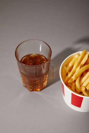 beer in glass near delicious french fries in bucket on grey background
