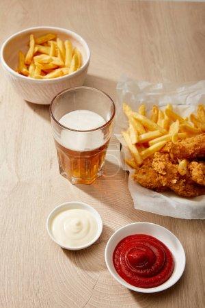 vaso de cerveza, nuggets de pollo con papas fritas, ketchup y mayonesa sobre mesa de madera