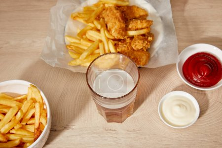 glass of beer, chicken nuggets with french fries, ketchup and mayonnaise on wooden table