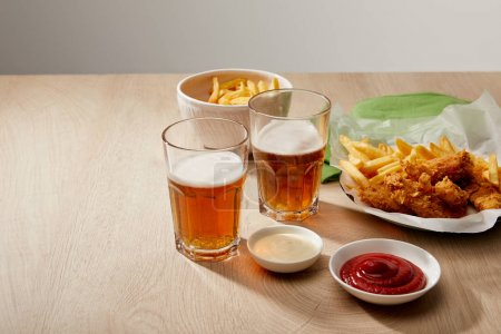 Photo for Glasses of beer, chicken nuggets with french fries, ketchup and mayonnaise on wooden table on grey background - Royalty Free Image