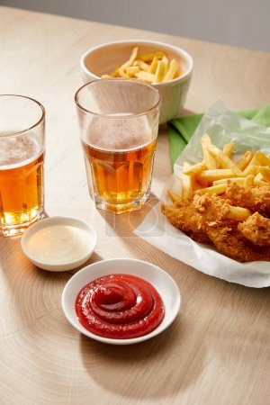 Foto de Glasses of beer, chicken nuggets with french fries, ketchup and mayonnaise on wooden table on grey background - Imagen libre de derechos