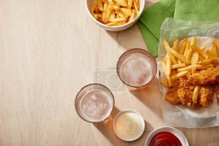 top view of glasses of beer, chicken nuggets with french fries, ketchup and mayonnaise on wooden table with copy space