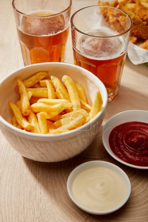 glasses of beer, french fries in bowl, sauces on wooden table