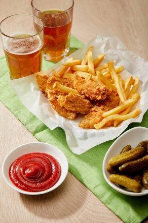 vasos de cerveza, nuggets de pollo con papas fritas, salsas y pepinillos sobre mesa de madera
