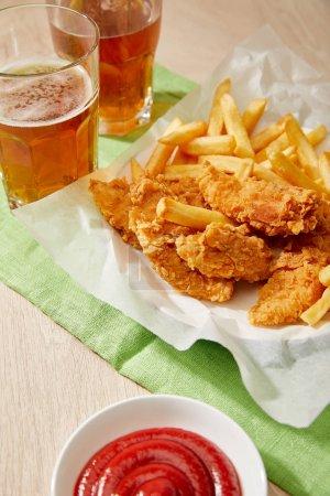Photo pour Verres de bière, pépites de poulet avec frites, ketchup sur table en bois - image libre de droit