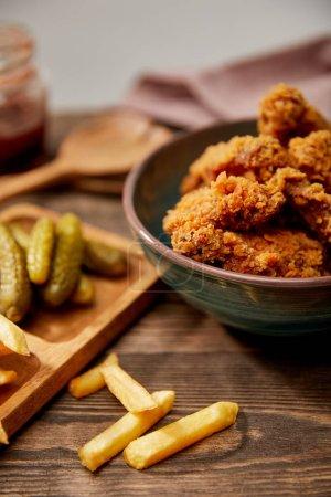 Photo pour Une sélection de délicieuses pépites de poulet, frites et cornichons sur table en bois - image libre de droit