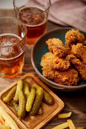 Photo for Delicious chicken nuggets, french fries and gherkins near glasses of beer on wooden table - Royalty Free Image