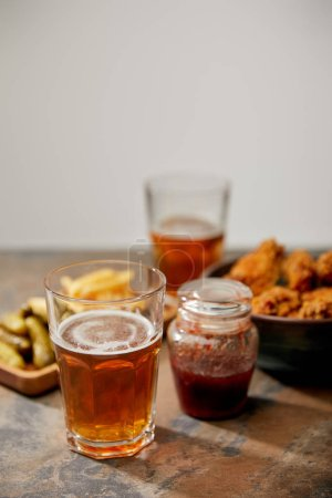 Photo for Selective focus of chicken nuggets, french fries and gherkins near glasses of beer on stone surface isolated on grey - Royalty Free Image