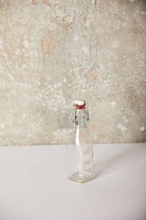 Photo pour Bouteille de verre vide près de la pierre mur gris - image libre de droit