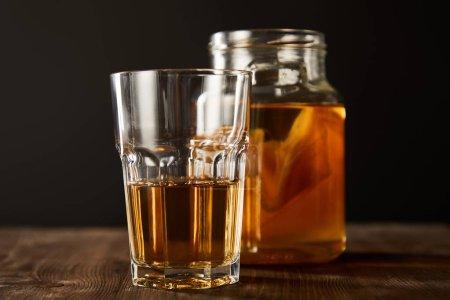 Foto de Foco selectivo de vidrio y jarro con kombucha en la mesa de madera aislada en negro. - Imagen libre de derechos