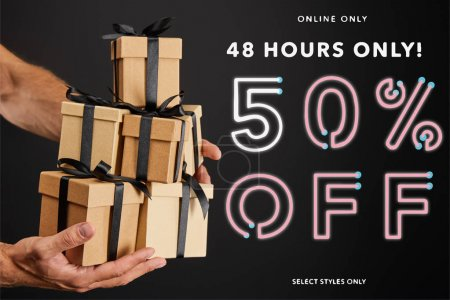 cropped view of man holding cardboard gift boxes with ribbons isolated on black with 48 hours 50 percent off illustration, black Friday concept