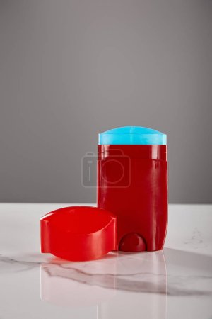 Photo for Red roll on bottle of deodorant on marble table isolated on grey - Royalty Free Image