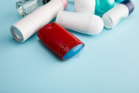 Photo pour Rouler et vaporiser des bouteilles de déodorant sur fond bleu avec espace de copie - image libre de droit
