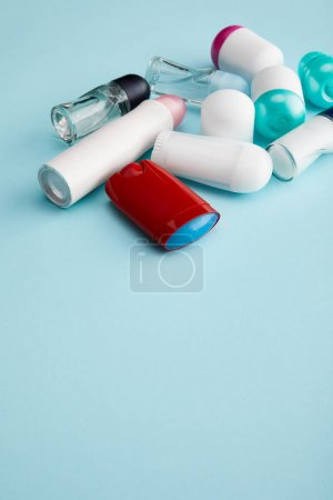 roll on and spray bottles of deodorant on blue background with copy space