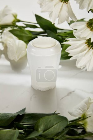 Photo for Selective focus of roll on bottle of deodorant with flowers on white surface - Royalty Free Image