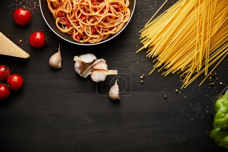 Photo for Top view of tasty bolognese pasta in frying pan on black background with fresh ingredients - Royalty Free Image