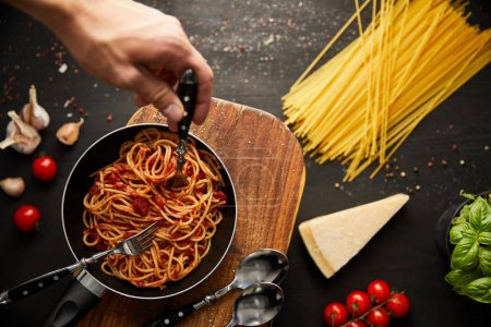 Photo for Cropped view of man putting fork in tasty bolognese pasta in frying pan on black background - Royalty Free Image