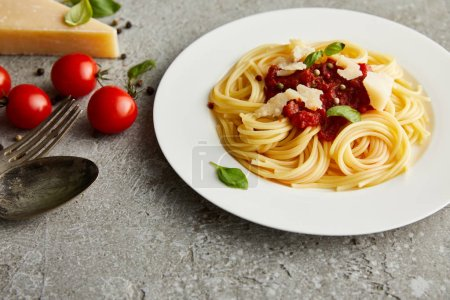 Photo for Tasty bolognese pasta with tomato sauce and Parmesan on white plate near ingredients and cutlery on grey background - Royalty Free Image