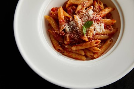 Photo for Top view of tasty bolognese pasta with tomato sauce and Parmesan in white plate isolated on black - Royalty Free Image