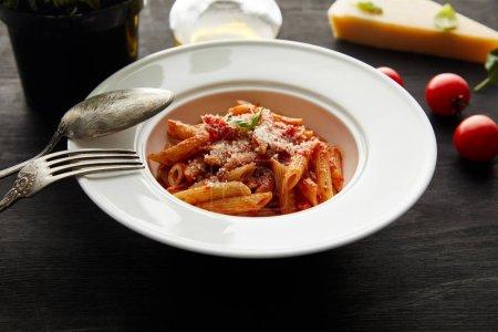 Photo pour Mise au point sélective de pâtes bolognaises savoureuses avec sauce tomate et parmesan dans une assiette blanche près des ingrédients et de la coutellerie sur fond de bois noir - image libre de droit