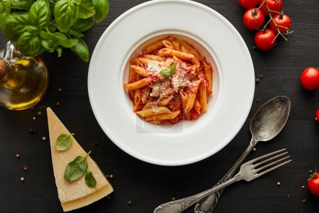 top view of tasty bolognese pasta with tomato sauce and Parmesan in white plate near ingredients and cutlery on black wooden background