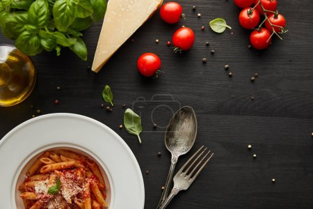 Photo for Top view of tasty bolognese pasta with tomato sauce and Parmesan in white plate near ingredients and cutlery on black wooden background - Royalty Free Image