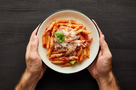 Photo for Cropped view of man holding plate with tasty bolognese pasta with tomato sauce and Parmesan on black wooden background - Royalty Free Image