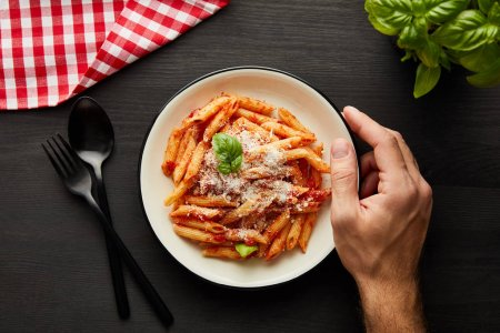 Photo for Cropped view of man holding plate with tasty bolognese pasta on black wooden table with basil, cutlery and check napkin - Royalty Free Image
