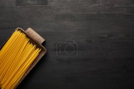 Photo for Top view of raw spaghetti on black wooden background - Royalty Free Image