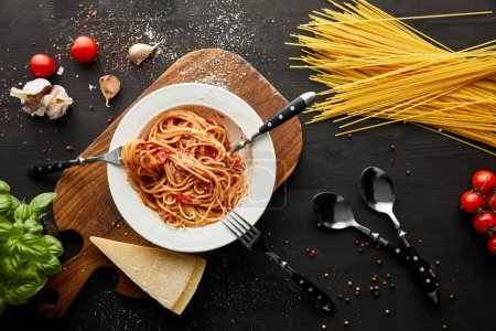 Photo for Top view of tasty bolognese pasta in white plate near ingredients and cutlery on black wooden background - Royalty Free Image
